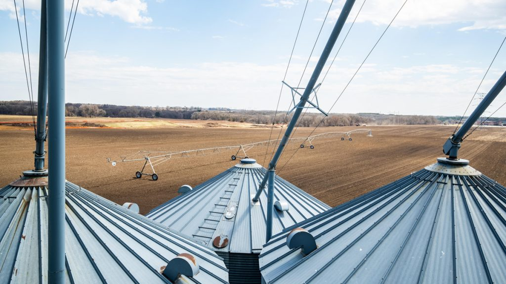Aerial view from above grain bins looking down into a field