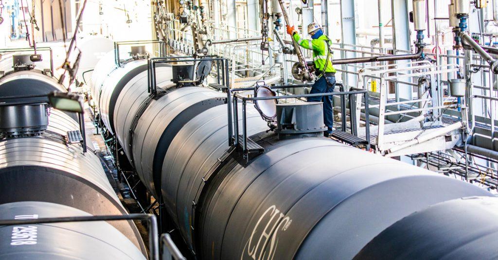 A worker in PPE loads a fuel tank rail car