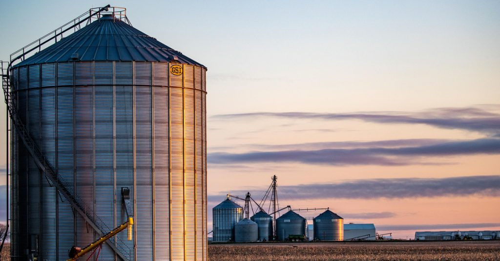 A landscape with grain bins at sunrise